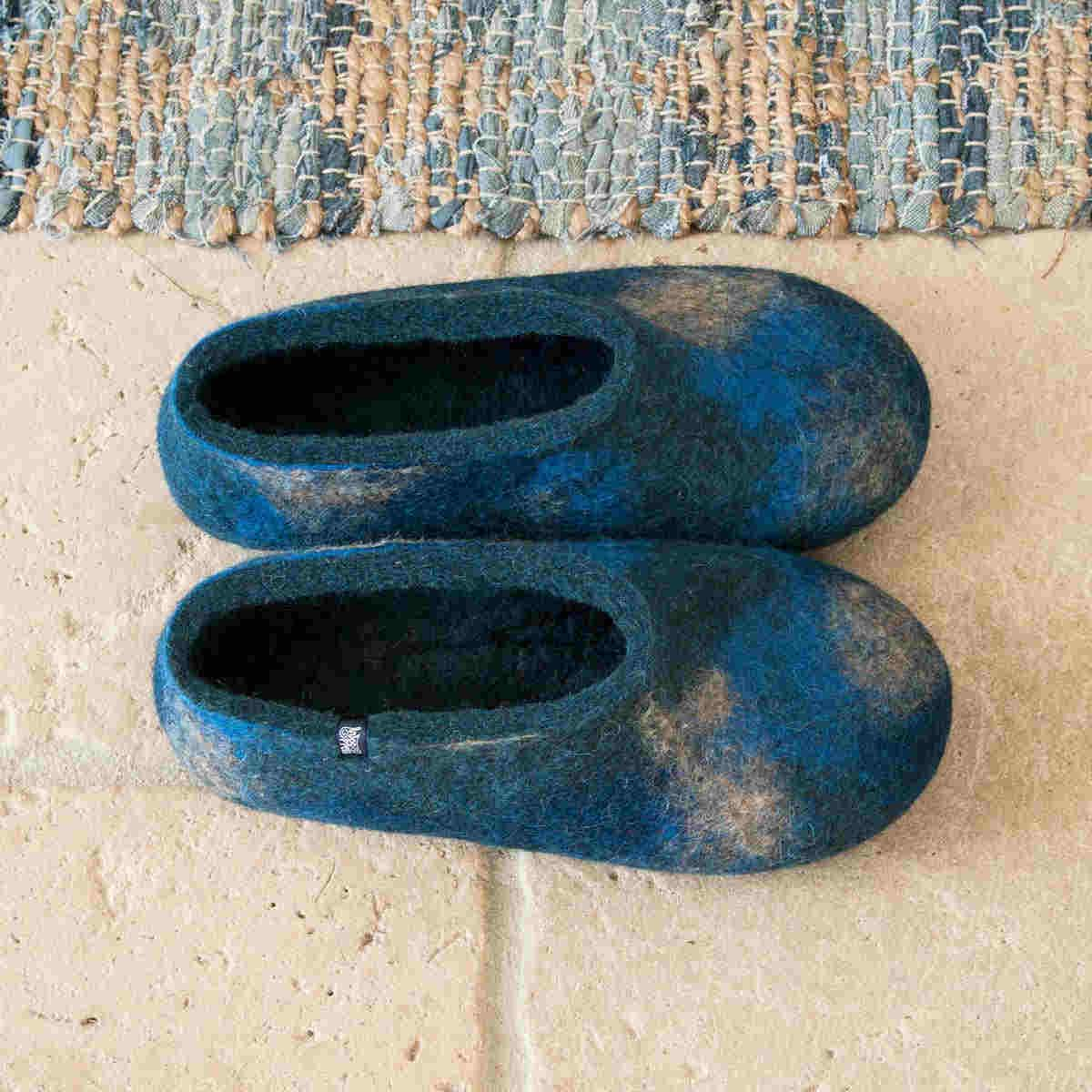 Handmade wool slippers in blue hues on the floor by Wooppers -