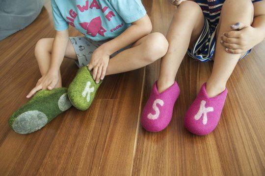 two kids with monogrammed slippers