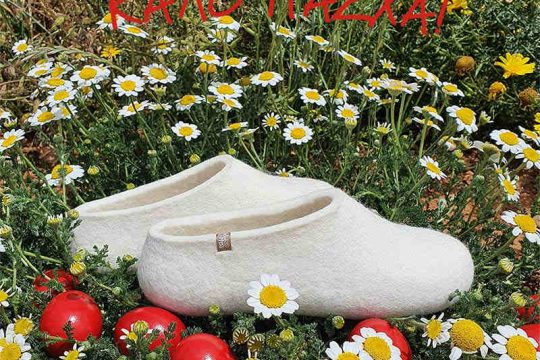 A pair of white wool slippers by Wooppers set on a wild flowers and daisies and scattered Easter eggs